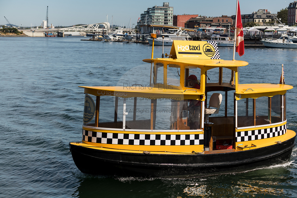 A tiny harbor yellow water taxi at the inner harbor in Victoria, BC, Canada.