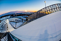 The world famous Holmenkollen  ski jump, Oslo, Norway (aka Holmenkollbakken.) It has been a site for ski jumping since 1892. The stadium has a capacity of 70,000 spectators. Between 2009 and 2010 the entire structure was demolished and rebuilt. It has been the site of numerous world championships and FIS Ski Jumping World Cup Events and was used in 1952 Winter Olympics.