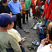 Children and adults watch demonstrations of toys at the main market in Antigua, Guatemala.