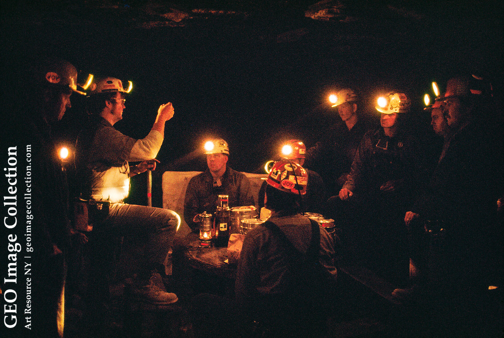 Coal miners hear a safety lecture while deep underground.