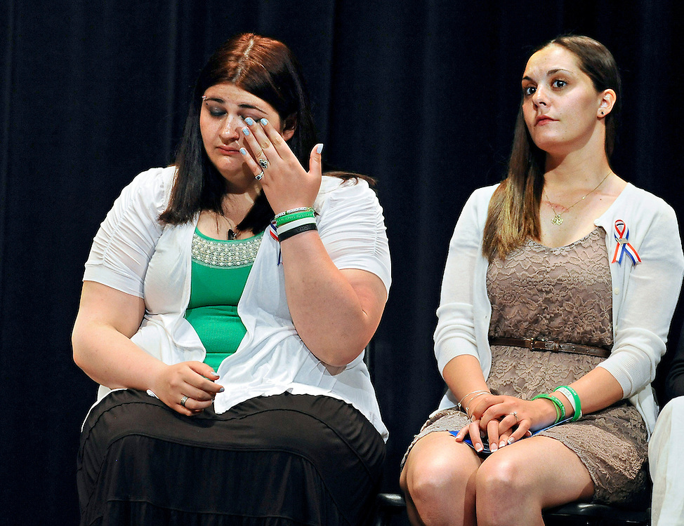 Hannah D'Avino, sister of Sandy Hook Elementary School shooting victim Rachel D'Avino, left, wipes a tear as Erica Lafferty, daughter of principal Dawn Hochsprung, right, looks on during a ceremony awarding the families the citizen honor of the Congressional Medal of Honor on behalf of in Newtown, Conn., Monday, May 6, 2013. The Congressional Medal of Honor Society says Rachel D'Avino, Dawn Hochsprung, Anne Marie Murphy, Lauren Rousseau, Mary Sherlach and Victoria Soto exemplified courage, sacrifice and selflessness in trying to protect students from the gunman at Sandy Hook Elementary School. (AP Photo/Jessica Hill)