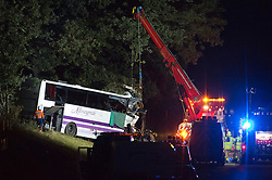 © London News Pictures. 11/09/2012. Hindhead, UK . The mangled remains of the bus being recovered from the roadside.  The scene of a fatal bus crash on the north bound A3 motorway near Hindhead Tunnel, Hindhead, Surrey on September 11, 2012.Three people were killed and a number of others seriously injured when a coach carrying overturned after crashing into a tree. Photo credit: Ben Cawthra/LNP