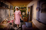 An elderly african-american woman sings gospel and blues tunes on the screened porch of her house.