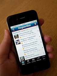 reading Guardian newspaper on an Apple iphone 4G smartphone