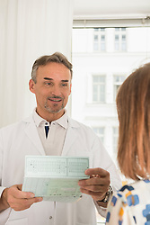 Doctor holding medical record and talking to patient in hospital, Munich, Bavaria, Germany