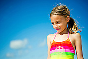 A young girl looks down while standing in front of a cloudy blue sky