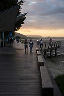 People walk at sunset on the Cairns Esplanade in Queensland, Australia (August 2017)