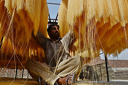 June 15, 2017 - Lahore, Punjab, Pakistan - Pakistani worker spreading the thin vermicelli ( Sevaian) for drying at a factory in the holy fasting month  of Ramzan purpose, prepared for the upcoming Eidul Fit. Muslims all over the world used to make a traditional sweet dish 'sheerkhurma'popular during the Islamic holy month of Ramadan. (Credit Image: © Rana Sajid Hussain/Pacific Press via ZUMA Wire)
