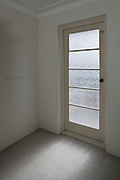 Light shines through a frosted glass door in a bare room