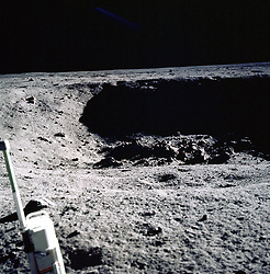 This is a photograph taken by Apollo 11 astronaut Neil Armstrong looking into East Crater, about 60 meters away from the lunar module. He estimated the crater was about 20 to 25 meters in diameter and 4 1/2 to 6 meters deep. The crater wall in the background is in deep shadow. The object at lower left is the stereo close-up camera. The view is roughly towards the northeast. Photo by CNP/ABACAPRESS.COM