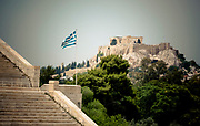 The Parthenon on the Acropolis (Greek for highest point) of Athens in the distance, as viewed from the original Olympic stadium with a Greek flag blowing in the wind