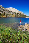 Child (age 5) standing on the shore of Long Lake, John Muir Wilderness, Sierra Nevada Mountains, California