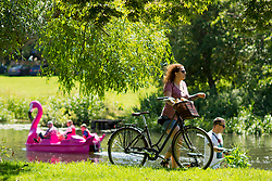 © Licensed to London News Pictures. 22/06/2019. Warwick, Warwickshire, UK. A woman pushes her bike along the river bank as people on a pedalo enjoy the weather on the river Avon in Warwick during a hot summers day. Photo credit: LNP