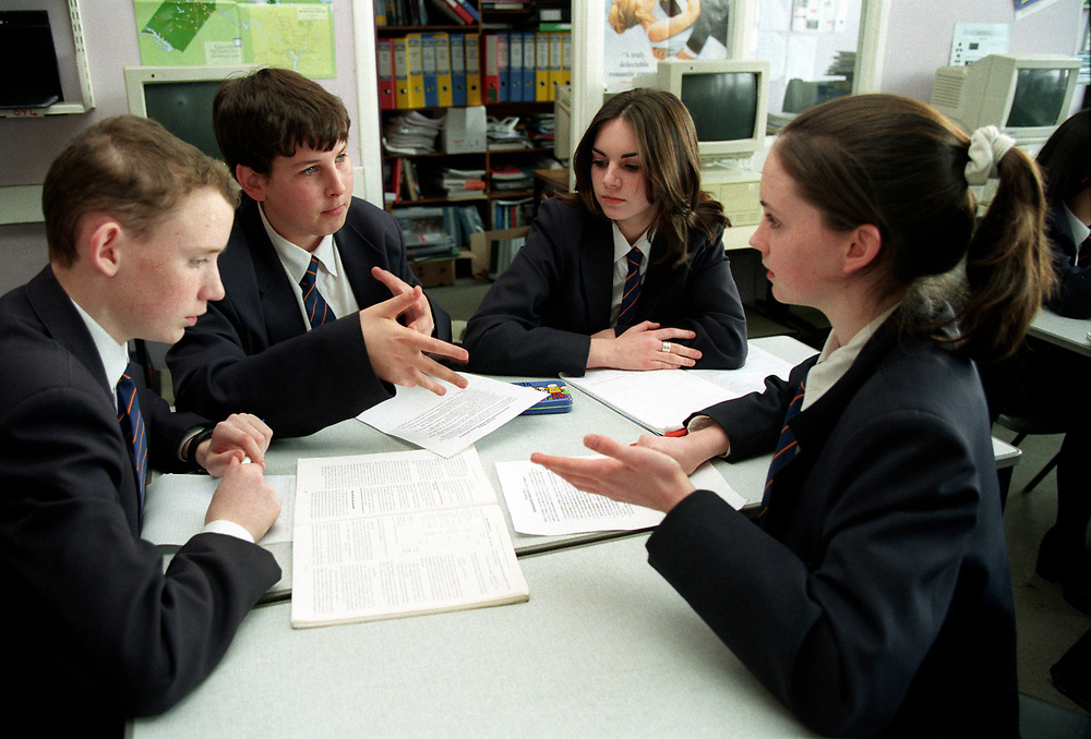 Secondary school pupils discussing their school work,