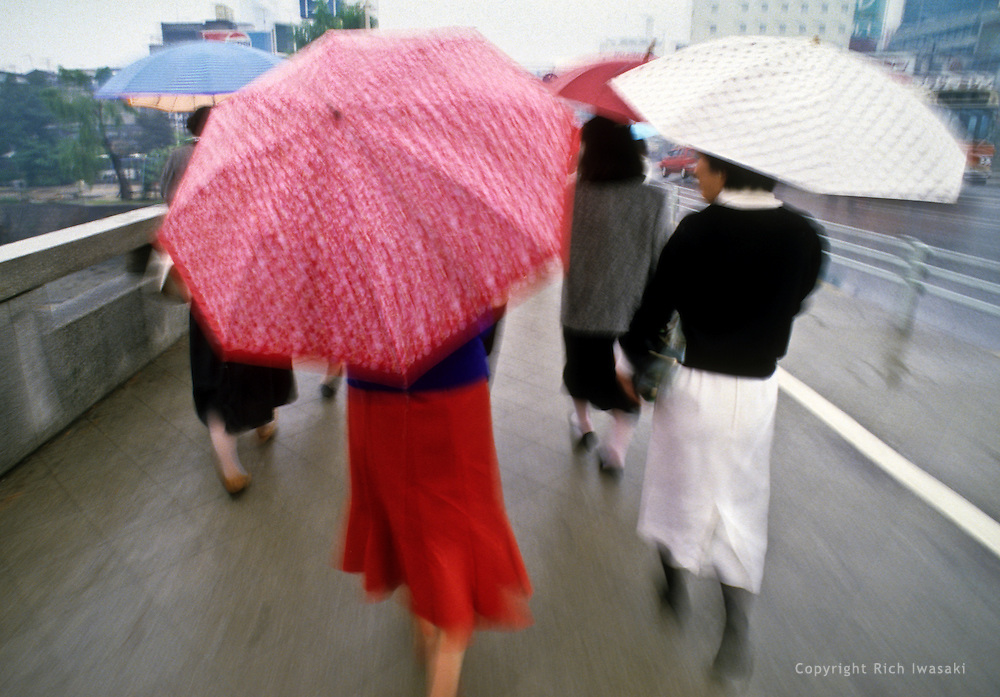 Blurred motion view of pedestrians with umbrellas walking in downtown Hiroshima, Hiroshima Prefecture, Japan