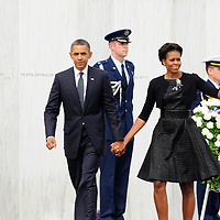 """President Barack Obama walks hand in hand as First Lady Michele Obama waves to family members after placing a wreath along the """"Wall of Names""""  at the Flight 93 National  Memorial on September 11, 2001. The white marble wall placed on the flight path of the crashed airplane has the names of the 40 victims of Flight 93 that perished in a terrorist attacks of 10 ten ago near the small town of Shanksville Pennsylvania.. UPI/Archie Carpenter"""
