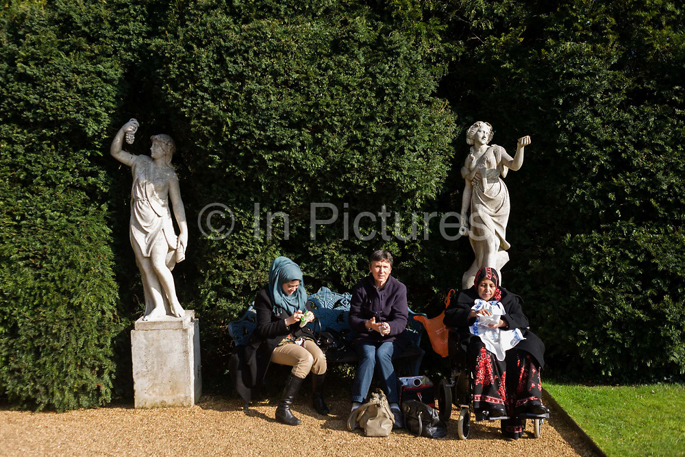 Two Muslim ladies and a European woman sit in sunshine at the National Trust's Hughenden Manor property gardens, once home to Benjamin Disraeli. This may be a day trip for the women to this old property - once a Tudor farmhouse - but now billed as Disraeli's country home during his time as Queen Victoria's Prime Minister who lived here from 1848 to 1881. The formal garden which was designed by Lady Beaconsfield has been restored to a similar condition to when occupied by the Disraelis. The long terrace at the rear of the house is decorated with Florentine vases.