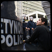 School pupils protesting in front of Greek police HQ in Alexandras avenue. <br /> <br /> Following the murder of a 15 year old boy, Alexandros Grigoropoulos, by a policeman on 6 December 2008 widespread riots, protests and unrest followed lasting for several weeks and spreading beyond the capital and even overseas<br /> <br /> When I walked in the streets of my town the day after the riots I instantly forgot the image I had about Athens, that of a bustling, peaceful, energetic metropolis and in my mind came the old photographs from WWII, the civil war and the students uprising against the dictatorship. <br /> <br /> Thus I decided not to turn my digital camera straight to the destroyed buildings but to photograph through an old camera that worked as a filter, a barrier between me and the city.