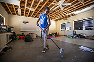 Jessica Bobo, 14, sweeps up debris in a classroom at Central Abaco Primary school where she continues to live with family after her home was destroyed by Hurricane Dorian at Marsh Harbour on Abaco Island on Saturday, September 7, 2019. The family is still at the temporary shelter.