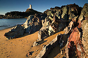 Amazing coloured Precambrian pillow lavas remain hard fingers of rock pushing into the soft sand and battering Irish Sea, here on a tiny island off the main island of Ynys Môn (Anglesey). <br /> <br /> The lighthouse (Twr Mawr)  is no longer used but it's presence is still a useful navigational mark for mariners.
