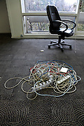 pile of assorted computer and electric cables on floor in empty room with office chair