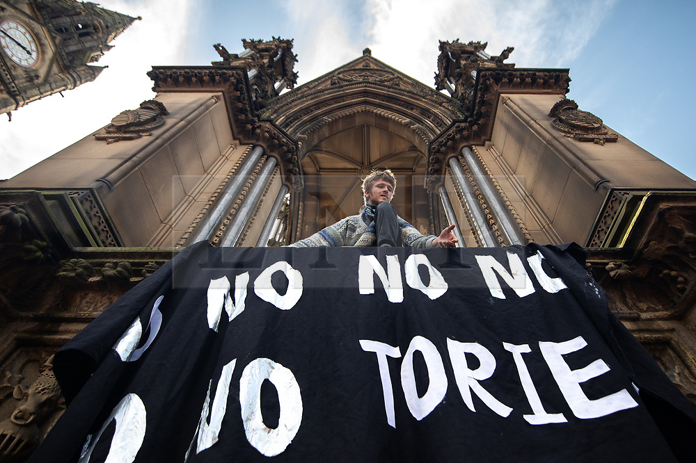 """© Licensed to London News Pictures. 31/08/2019. Manchester, UK. A man raises a banner reading """" No no no no no no tories"""" on the Albert Memorial at a pro-EU demo at Albert Square in Manchester City Centre , as objections are raised to the Prime Minister Boris Johnson's intention to prorogue Parliament in the run up to Britain's planned Brexit deadline . Photo credit: Joel Goodman/LNP"""