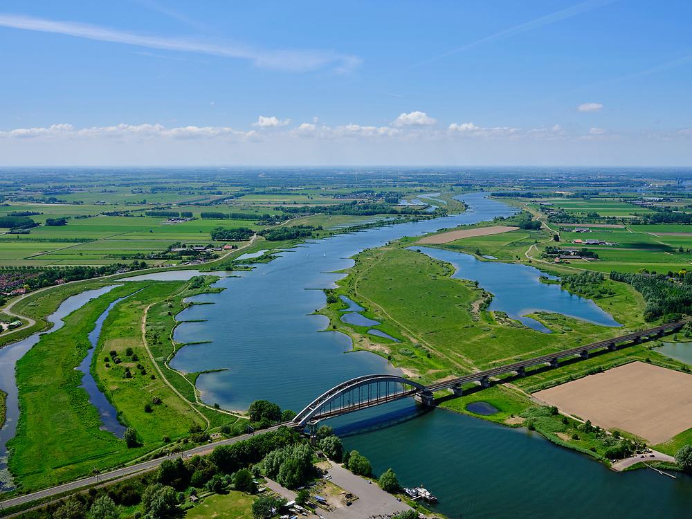 Nederland, Gelderland, Gemeente Culemborg, 27-05-2020; Rivier de Lek en spoorbrug Culemborg (Kuilenburgse spoorbrug). <br /> In de Goilberdingerwaard en Steenwaard (rechts) is de zomerdijk verlaagd en gedeeltelijk weggegraven en ook zijn in de uiterwaard geulen gegraven om rivier de Lek bij hoogwater meer de ruimte te geven.<br /> Railway bridge Culemborg and Lek River. In the floodplains the summer dike has been reduced in height and partially excavated, and trenches haven been dug to create 'room for the river' at heigh waters.<br /> luchtfoto (toeslag op standaard tarieven);<br /> aerial photo (additional fee required)<br /> copyright © 2020 foto/photo Siebe Swart