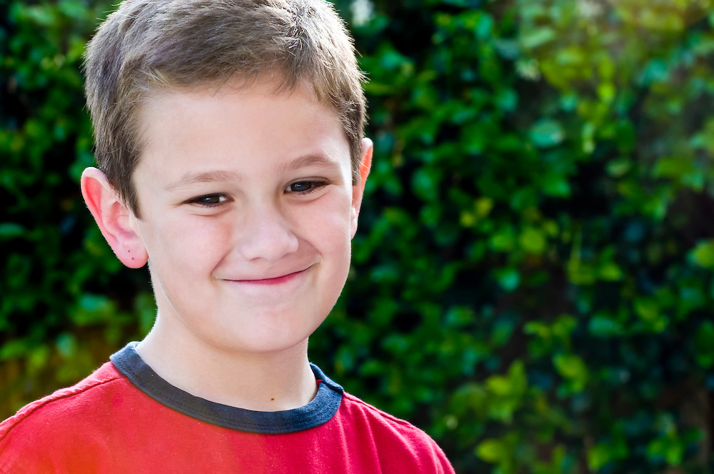 Portrait of young caucasian kid smiling in the summer.