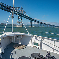 """The USS Potamac, once President Franklin D. Roosevelt's """"Floating White House,"""" is now preserved  as a museum and offers tours of San Francisco Bay, California.  Here it is passing under the San Rafael Bridge."""