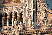 Detail of religious statues and gargoyles on Il Duomo di Siena, the Cathedral of Siena, Italy.