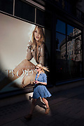 A young woman walks through a pool of sunlight in front of a giant Burberry poster girl ad of the actress Rosie Alice Huntington-Whiteley in central London. It is lunchtime and the woman passes-by with a snack and a coffee, wearing a blue dress and with her long blonde hair trailing in the afternoon breeze. Burberry Group plc is a British luxury fashion house, manufacturing clothing, fragrance, and fashion accessories. Rosie Alice Huntington-Whiteley (born 18 April 1987) is an English model and actress unveiled as the face of Burberry's newest fragrance, Burberry Body, in July 2011 but also best known for her work for Victoria's Secret, Burberry, and her role as Carly Spencer in the 2011 film Transformers: Dark of the Moon, part of the Transformers film series