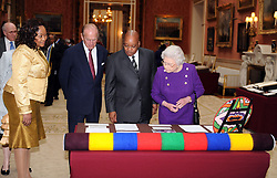 Britain's Queen Elizabeth II, Prince Philip, Duke of Edinburgh, President of South Africa Jacob Zuma and Mrs Zuma look at a woollen blanket woven in the colours of South Africa, part of an exhibition of South African related items at Buckingham Palace in London as part of the President's three-day state visit.