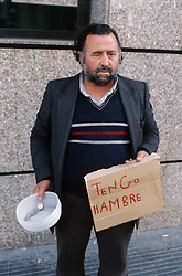 Man begging in street in Barcelona; holding sign reading 'tengo hambre'  I am hungry,