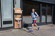 As the second week of the Coronavirus lockdown continues around the capital, and the UK death toll rising by 563 to 2,325, with 800,000 reported cases of Covid-19 worldwide, a man runs past a free handwash station fitted for the benefit of the public outside a local business in Clapham High Street, on 1st April 2020, in London, England.
