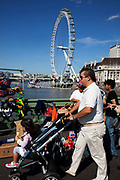 Tourist man pushing a little girl in a pram cross Westminster bridge by the River Thames at Westminter, London. With the iconic London Eye behind this is one of the busiest areas for tourism in the city.