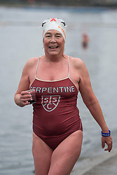 © Licensed to London News Pictures. 25/12/2017. London, UK. A competitor carrying drink of 'Nelsons Bloodd', given to all swimmers after the race. Members of the Serpentine Swimming Club brave the cold waters at the Serpentine Lake in Hyde Park, London to compete for the traditional Peter Pan Cup on Christmas Day, December 25, 2017. Photo credit: Ben Cawthra/LNP