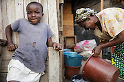 A young girl rests against the wall while her mother does laundry in the Campement neighborhood of Abidjan, Cote d'Ivoire on Wednesday July 10, 2013.