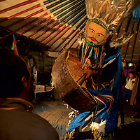 MONGOLIA, Darhad Valley. A shaman (Batsuur) dances, chants and beats his drums to invoke spirits during a trance in his ger (yurt).