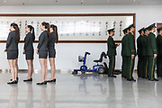 Show hostesses and Chinese Peoples Liberation Army soldiers line up for separate row calls ahead of the Beijing International Automotive Exhibition in Beijing, China, on Monday, April 25, 2016. China is leading the way to move towards new energy vehicles especially electrification as it sees an opportunity to leap frog traditional powerhouses in the automobile industry.