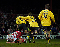 Photo: Jed Wee.<br /> Doncaster Rovers v Arsenal. Carling Cup. 21/12/2005.<br /> <br /> Doncaster's Ricky Ravenhill crouches in disappointment as Arsenal celebrate their late equaliser.