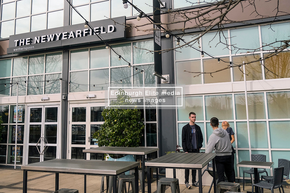 """Livingston During Coronavirus Outbreak, 21 March 2020<br /> <br /> Cafes, pubs and restaurants have been ordered to close, to tackle coronavirus. Nightclubs, theatres, cinemas, gyms and leisure centres must do so """"as soon as they reasonably can"""", the government said.<br /> <br /> These steps are part of the UK's social distancing measures.<br /> <br /> Everybody is being asked to avoid non-essential contact with other people.<br /> <br /> Pictured: Weatherspoon's """"The Newyearfield"""" pub in Livingston ignored the government's advice to close. Staff are seen breaking social distancing advice by having a cigarette break together<br /> <br /> Alex Todd 
