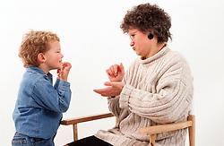 Mother with hearing impairment using sign language to communicate with young son,
