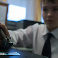 Boy stamps a ticket at the cashier desk of the Huvosvolgy station of the Children's Railway in Budapest, Hungary on November 13, 2014. ATTILA VOLGYI