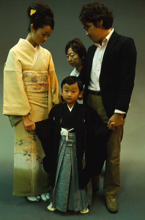 A young boy and his  parents get ready to pose for the camera in a photographer's studio before going to a Shinto shrine for the boy's shichi-go-san ritual in Tokyo, Japan. During shichi-go-san, literally seven-five-three, parents dress their daughters aged three and seven and sons aged five in traditional costume and take them to a Shinto shrine to be blessed.