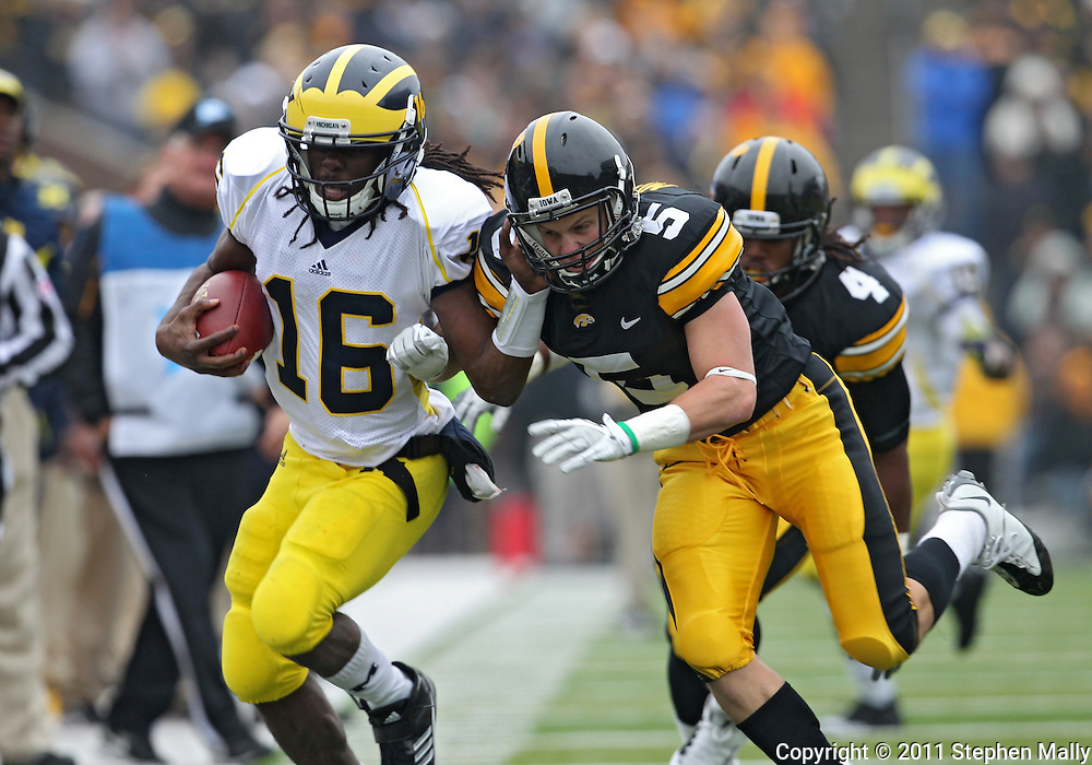 November 05, 2011: Michigan Wolverines quarterback Denard Robinson (16) tries to hold off Iowa Hawkeyes defensive back Tanner Miller (5) as he runs with the ball during the second half of the NCAA football game between the Michigan Wolverines and the Iowa Hawkeyes at Kinnick Stadium in Iowa City, Iowa on Saturday, November 5, 2011. Iowa defeated Michigan 24-16.