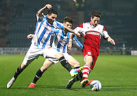 Middlesbrough's Jacob Butterfield holds off the challenge from Huddersfield Town's Adam Hammill (left) and Oliver Norwood<br /> <br /> Photo by Rich Linley/CameraSport<br /> <br /> Football - The Football League Sky Bet Championship - Huddersfield Town v Middlesbrough - Tuesday 25th March 2014 - The John Smith's Stadium - Huddersfield<br /> <br /> © CameraSport - 43 Linden Ave. Countesthorpe. Leicester. England. LE8 5PG - Tel: +44 (0) 116 277 4147 - admin@camerasport.com - www.camerasport.com