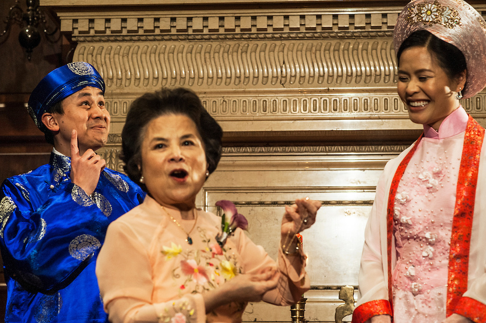 Photo by Matt Roth.Assignment ID: 10137951A..Daniel Tran Gien, left, makes a humorous gesture while his mother, Dr. Lan Gien, foreground, explains to the crowd that the origin of the necklace she is about to present to her new daughter-in-law Caroline Trang Nguyen, right, is from Vietnam. Before their reception, the couple held a private traditional Vietnamese tea ceremony at the Carnegie Institution for Science in Washington, D.C. on Saturday, February 02, 2013.