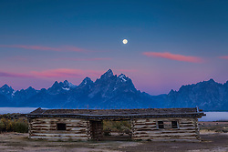 """Setting moon at sunset over the Grand Tetons and the Cunningham Cabin in Grand Teton National Park.  The Cunningham Cabin was one of the original homsteader cabins of Jackson Hole Wyoming<br /> <br /> For production prints or stock photos click the Purchase Print/License Photo Button in upper Right; for Fine Art """"Custom Prints"""" contact Daryl - 208-709-3250 or dh@greater-yellowstone.com"""