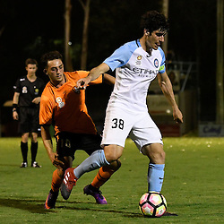 BRISBANE, AUSTRALIA - DECEMBER 22: Leo Athanasiou of Melbourne City dribbles the ball infront of Nicholas Panetta of the Roar during the round 4 Foxtel National Youth League match between the Brisbane Roar and Melbourne City at AJ Kelly Field on December 22, 2016 in Brisbane, Australia. (Photo by Patrick Kearney/Brisbane Roar)