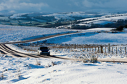 © Licensed to London News Pictures. 14/01/2016. Builth Wells, Powys, Wales, UK. Motorists drive through a winter landscape on the'Brecon Road' between Builth Wells and Brecon.About 5cm of snow fell last night on the high moorland of the Mynydd Epynt, near Builth Wells, Powys, Wales. Photo credit: Graham M. Lawrence/LNP